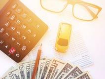 Μικροσκοπικά πρότυπο αυτοκινήτων, μολύβι, υπολογιστής, eyeglasses, χρήματα και βιβλιάριο ή οικονομική κατάσταση λογαριασμού ταμιε Στοκ Εικόνες