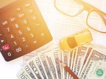 Μικροσκοπικά πρότυπο αυτοκινήτων, μολύβι, χρήματα, υπολογιστής, eyeglasses και βιβλιάριο ή οικονομική κατάσταση λογαριασμού ταμιε Στοκ φωτογραφίες με δικαίωμα ελεύθερης χρήσης