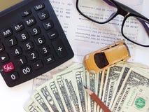 Μικροσκοπικά πρότυπο αυτοκινήτων, μολύβι, χρήματα, υπολογιστής, eyeglasses και βιβλιάριο ή οικονομική κατάσταση λογαριασμού ταμιε Στοκ εικόνα με δικαίωμα ελεύθερης χρήσης