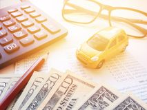 Μικροσκοπικά πρότυπο αυτοκινήτων, μολύβι, χρήματα, υπολογιστής, eyeglasses και βιβλιάριο ή οικονομική κατάσταση λογαριασμού ταμιε Στοκ Φωτογραφίες