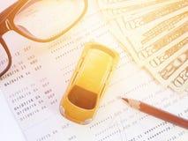 Μικροσκοπικά πρότυπο αυτοκινήτων, μολύβι, eyeglasses, χρήματα και βιβλιάριο ή οικονομική κατάσταση λογαριασμού ταμιευτηρίου στο ά Στοκ Εικόνες