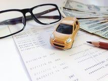 Μικροσκοπικά πρότυπο αυτοκινήτων, μολύβι, eyeglasses, χρήματα και βιβλιάριο ή οικονομική κατάσταση λογαριασμού ταμιευτηρίου στο ά Στοκ φωτογραφίες με δικαίωμα ελεύθερης χρήσης