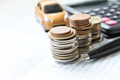 Μικροσκοπικά πρότυπο αυτοκινήτων, υπολογιστής, νομίσματα και βιβλίο ή οικονομική κατάσταση απολογισμού αποταμίευσης στον πίνακα γ Στοκ Εικόνα