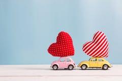 Μικροσκοπικά ρόδινα και κίτρινα αυτοκίνητα που φέρνουν τα μαξιλάρια καρδιών Στοκ εικόνες με δικαίωμα ελεύθερης χρήσης