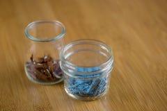 Μικροσκοπικές ζωηρόχρωμες καρφίτσες στα βάζα γυαλιού στη μακροεντολή με το ξύλινο υπόβαθρο Στοκ Εικόνες