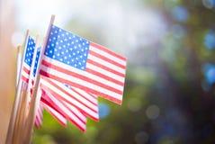 Μικροσκοπικές σημαίες ΗΠΑ εγγράφου Αμερικανική σημαία στο θολωμένο υπόβαθρο υπαίθρια στοκ εικόνα με δικαίωμα ελεύθερης χρήσης