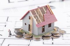 Μικροσκοπικές στάσεις σπιτιών στα νομίσματα Η έννοια των τραπεζικών εργασιών, δάνεια, Στοκ Φωτογραφία