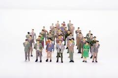 Μικροσκοπική επιχείρηση ανθρώπων που στέκεται στο πλήθος πέρα από το άσπρο σκηνικό Στοκ Φωτογραφία