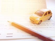 Μικροσκοπική πρότυπο αυτοκινήτων, μολύβι και βιβλιάριο ή οικονομική κατάσταση λογαριασμού ταμιευτηρίου στο άσπρο υπόβαθρο Στοκ Φωτογραφία