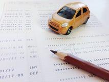 Μικροσκοπική πρότυπο αυτοκινήτων, μολύβι και βιβλιάριο ή οικονομική κατάσταση λογαριασμού ταμιευτηρίου στο άσπρο υπόβαθρο Στοκ Εικόνες