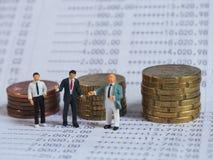 Μικροσκοπική στάση επιχειρηματιών στην τράπεζα βιβλίων, κοντά στο σωρό των νομισμάτων Bu στοκ εικόνα
