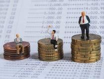 Μικροσκοπική στάση επιχειρηματιών στην τράπεζα βιβλίων, κοντά στο σωρό των νομισμάτων Bu στοκ εικόνες με δικαίωμα ελεύθερης χρήσης