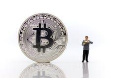 Μικροσκοπικοί άνθρωποι: Άτομα που διαβάζουν για τα χρήματα ευρημάτων με το bitcoin στο άσπρο υπόβαθρο στοκ φωτογραφία