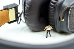 Μικροσκοπικοί άνθρωποι: Επιχειρηματίας με τα ακουστικά για το στούντιο μουσικής, Στοκ φωτογραφία με δικαίωμα ελεύθερης χρήσης