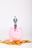 Μικροσκοπικοί άνθρωποι με τη piggy τράπεζα και το χρυσό νόμισμα Στοκ Φωτογραφία
