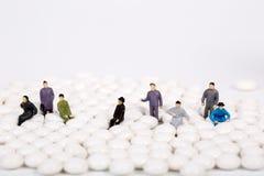 Μικροσκοπικοί άνθρωποι με το άσπρο χάπι Στοκ Εικόνες