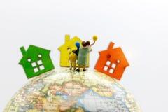 Μικροσκοπικοί άνθρωποι: Οικογένεια που στέκεται στη σφαίρα με τα σπίτια, ευτυχές φ Στοκ Εικόνα