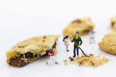Μικροσκοπικοί άνθρωποι: Οι εργαζόμενοι χρησιμοποιούν τη σκούπα κάνουν καθαρός των μπισκότων Χρήση εικόνας για την επιχειρησιακή έ Στοκ Φωτογραφίες