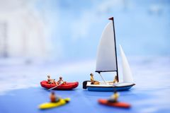 Μικροσκοπικοί άνθρωποι: οι άνθρωποι που κωπηλατούν τις βάρκες και που πλέουν τις βάρκες, χαλαρώνουν Στοκ εικόνα με δικαίωμα ελεύθερης χρήσης