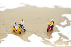 Μικροσκοπικοί άνθρωποι: οι άνθρωποι στο μηχανικό δίκυκλο με τον κόσμο χαρτογραφούν, ταξιδεύουν το conce Στοκ Φωτογραφία
