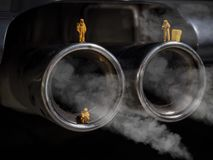 Μικροσκοπικοί άνθρωποι που εξετάζουν την εξάτμιση αυτοκινήτων στοκ φωτογραφία με δικαίωμα ελεύθερης χρήσης