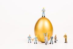Μικροσκοπικοί άνθρωποι που εργάζονται με το χρυσό αυγό Στοκ Φωτογραφίες