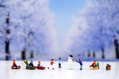 Μικροσκοπικοί άνθρωποι: Άνθρωποι χιονανθρώπων και παιδιών που παίζουν γύρω από το s Στοκ Εικόνες