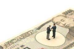 Μικροσκοπικοί 2 επιχειρηματίες ανθρώπων τινάζουν τη στάση χεριών στα ιαπωνικά τραπεζογραμμάτια αξίας 10.000 γεν χρησιμοποιώντας ω Στοκ Εικόνα