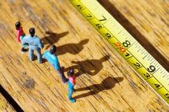 Μικροσκοπικοί μικροί άνθρωποι υπαίθρια με τη σκιά στο πάτωμα, μπροστά από ένα μέτρο ταινιών σε ένα ξύλινο υπόβαθρο Στοκ Εικόνες