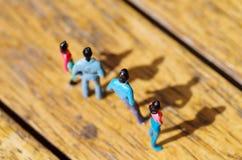 Μικροσκοπικοί μικροί άνθρωποι, φίλος υπαίθρια με τη σκιά στο πάτωμα, σε ένα ξύλινο υπόβαθρο Στοκ Εικόνες