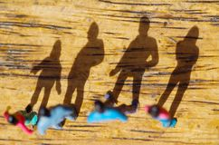 Μικροσκοπικοί μικροί άνθρωποι, φίλος υπαίθρια με τη σκιά στο πάτωμα, σε ένα ξύλινο υπόβαθρο, τοπ άποψη Στοκ φωτογραφίες με δικαίωμα ελεύθερης χρήσης