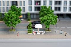 Μικροσκοπικοί πρότυποι, μικροσκοπικοί κτήρια παιχνιδιών, αυτοκίνητα και άνθρωποι Maquette πόλεων Στοκ Εικόνες