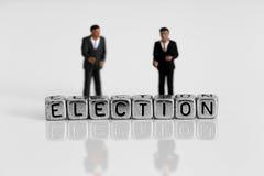 Μικροσκοπικοί πρότυποι πολιτικοί κλίμακας που στέκονται πίσω από τον υποψήφιο λέξης στοκ εικόνες