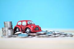 Μικροσκοπικοί πρότυπο αυτοκινήτων και σωρός νομισμάτων στον πίνακα γραφείων Στοκ Φωτογραφία