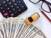 Μικροσκοπικοί πρότυπο αυτοκινήτων, υπολογιστής και χρήματα δολαρίων στον πίνακα γραφείων γραφείων Στοκ Εικόνες