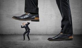 Μικροσκοπικός εκφοβισμένος επιχειρηματίας κάτω από τα πόδια του τεράστιου ατόμου Στοκ Εικόνες