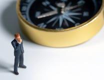 Μικροσκοπικός επιχειρηματίας αριθμού στο σκούρο μπλε κοστούμι που στέκεται στην πλευρά της χρυσής πυξίδας Έννοια για την εύρεση τ στοκ φωτογραφία με δικαίωμα ελεύθερης χρήσης