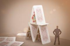 Μικροσκοπικός επιχειρηματίας που στέκεται κοντά στο σπίτι των καρτών Στοκ φωτογραφίες με δικαίωμα ελεύθερης χρήσης