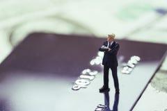 Μικροσκοπικός επιχειρηματίας στο κοστούμι που στέκεται και που σκέφτεται στην πιστωτική κάρτα που χρησιμοποιεί όπως on-line ψωνίζ στοκ φωτογραφίες