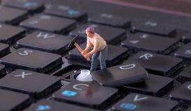 Μικροσκοπικός εργαζόμενος με την αξίνα που λειτουργεί στο πληκτρολόγιο Στοκ Εικόνες