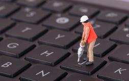 Μικροσκοπικός εργαζόμενος με το τρυπάνι που λειτουργεί στο πληκτρολόγιο Στοκ φωτογραφία με δικαίωμα ελεύθερης χρήσης
