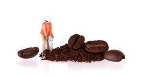 Μικροσκοπικός εργαζόμενος που εργάζεται σε ένα φασόλι καφέ Στοκ Φωτογραφία