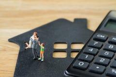 Μικροσκοπικός ευτυχής οικογενειακός αριθμός που στέκεται στο σπίτι εγγράφου με το calcu Στοκ Εικόνες