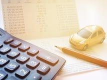 Μικροσκοπικός πρότυπο αυτοκινήτων, υπολογιστής και βιβλίο ή οικονομική κατάσταση απολογισμού αποταμίευσης στον πίνακα γραφείων γρ Στοκ Φωτογραφίες