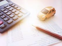 Μικροσκοπικός πρότυπο αυτοκινήτων, υπολογιστής και βιβλίο ή οικονομική κατάσταση απολογισμού αποταμίευσης στον πίνακα γραφείων γρ Στοκ φωτογραφία με δικαίωμα ελεύθερης χρήσης