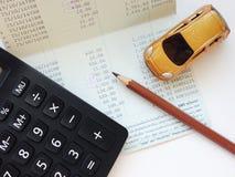 Μικροσκοπικός πρότυπο αυτοκινήτων, υπολογιστής και βιβλίο ή οικονομική κατάσταση απολογισμού αποταμίευσης στον πίνακα γραφείων Στοκ φωτογραφίες με δικαίωμα ελεύθερης χρήσης