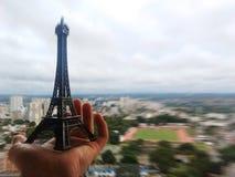 Μικροσκοπικός πύργος του Άιφελ σε ένα χέρι προσώπων ` s ενάντια στον ορίζοντα Στοκ Φωτογραφίες