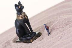 Μικροσκοπικός τουρίστας με το αιγυπτιακό άγαλμα Bastet φυλάκων Στοκ Εικόνες