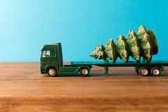 μικροσκοπικός Το φορτηγό παιχνιδιών φέρνει το χριστουγεννιάτικο δέντρο r Στοκ Εικόνες