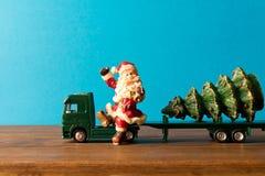 μικροσκοπικός Το φορτηγό παιχνιδιών φέρνει Santa και το χριστουγεννιάτικο δέντρο Το conce Στοκ Εικόνα